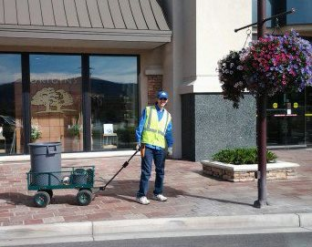 Dressed in his work vest and smiling at the camera, Ryan pulls a cart of gardening supplies along a sunny sidewalk.