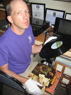 Brian, wearing white protective gloves and looking up at the camera, sits with a Jim Dawson record in his left hand and the record cover on his lap.