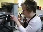 Emilea, wearing a black apron, stands in front of a machine in the coffee shop, with her left hand using the machine to fill the cup held in her right hand.