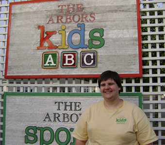 Taking steps from part-time classroom assistant toward full-time childcare professional Nicole smiles in front of a colorful sign for The Arbors Kids.