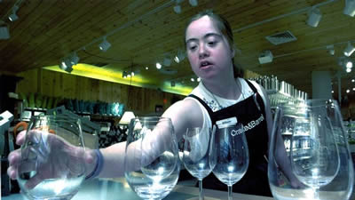 Wearing a black 'Crate & Barrel' apron, Allison reaches over a display of wine glasses and grasps one with her left hand.