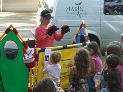Dusty, who stands in front of a colorful makeshift barrier, wearing a puppet on each hand, is watched by a group of children.