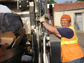 Dressed in orange vest and backwards orange hat, Frankie stands with both gloved hands holding onto the side of a truck and smiles towards the camera.