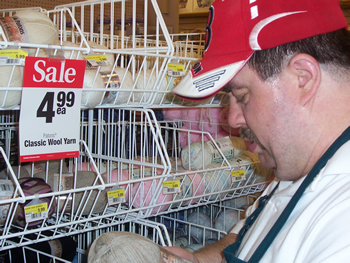In this close-up photo, John looks down at a yarn product in his hand, as he stands in front of a sales display and sign, indicating that 'Classic Wool Yarn' is on sale.
