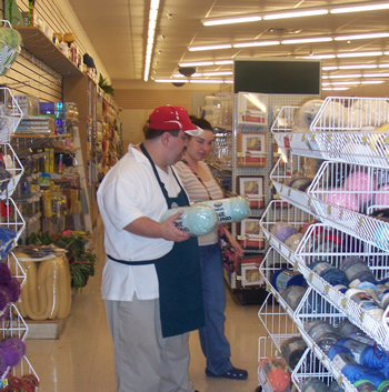 Dressed in his Jo-Ann's Fabrics apron and a red hat, John stands in an aisle facing a sales display full of yarn and holds a yarn product in each hand, while a woman stands to his left looking at the yarn display.
