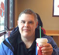Seated in a cafe, Ken faces the camera and holds up a Starbucks beverage.