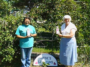 Standing in the sun in front of some trees and bushes, Melissa and her mother each hold a package of gourmet dog biscuits and stand on either side of a 'Lissie's Luv Yums' sign.